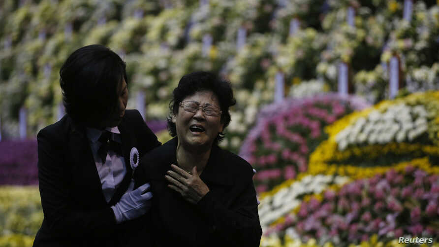 A mourner cries while assisted by an usher as she pays tribute to victims of sunken passenger ship Sewol, at the official memorial altar for the victims in Ansan, April 29, 2014.