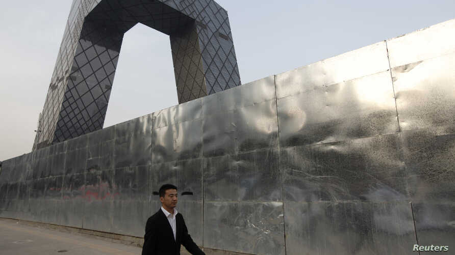 FILE - A man walks outside a construction site, next to the China Central Television (CCTV) building in Beijing's central business district.