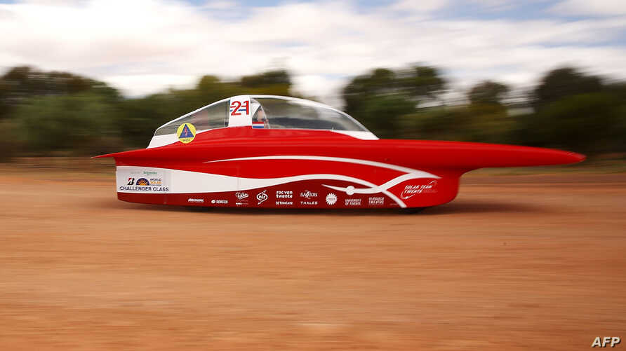 """This handout from the World Solar Challenge taken and received on October 11, 2017, shows the Solar Team Twente vehicle """"RED Shift"""" of Netherland in action near Coober Pedy on the fourth day of racing."""