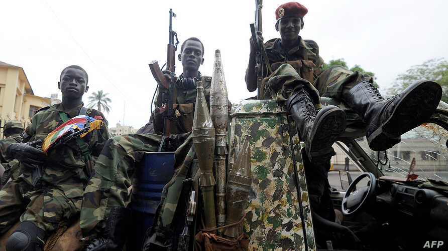 FILE - Child soldiers of the Seleka coalition sits on a pickup truck near the Presidential palace in Bangui, March 25, 2013.