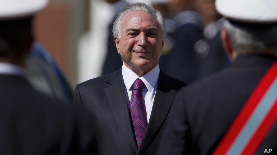 Brazil's President Michel Temer smiles as he receives military honors during a ceremony, in Brasilia, June 9, 2017.