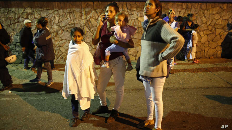 "Residents stand outside their apartments in a street near the ""Tower of David"" skyscraper, which suffered an inclination after a powerful earthquake shook eastern Venezuela, causing buildings to be evacuated in the capital of Caracas, Aug. 21, 2018."