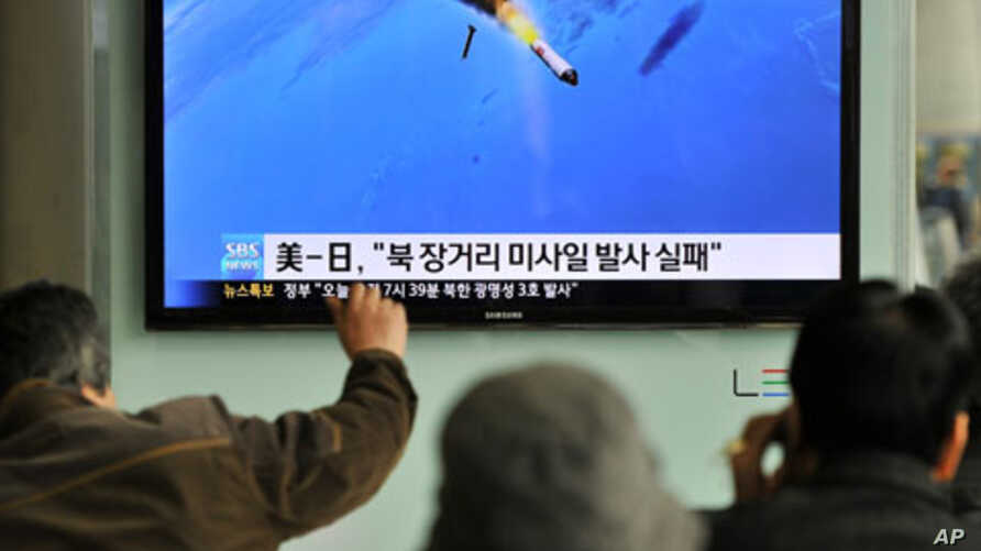 South Korean people watch a TV screen showing a graphic of North Korea's rocket launch, at a train station in Seoul, April 13, 2012.