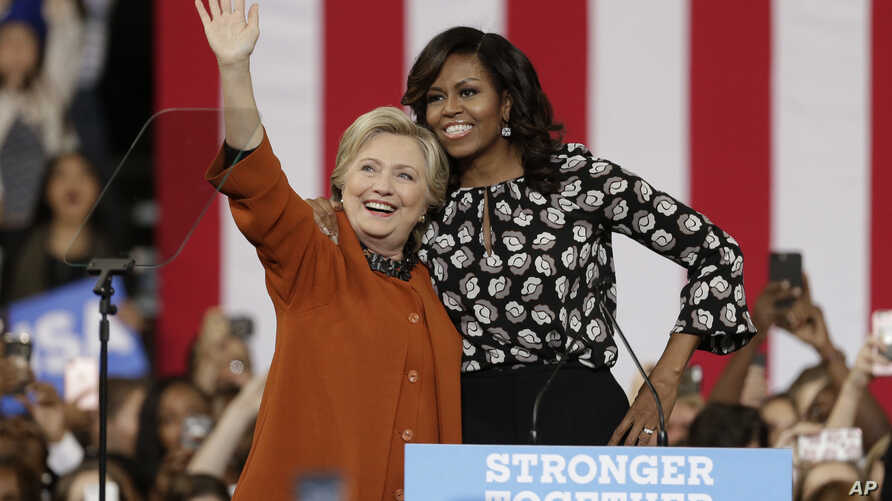 Democratic presidential candidate Hillary Clinton, accompanied by first lady Michelle Obama, greet supporters during a campaign rally in Winston-Salem, N.C., Oct. 27, 2016.