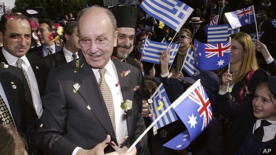 FILE - Then-President of Greece Constantine Stephanopoulos is greeted by school children, waving Greek and Australian flags and throwing flower petals, as he arrives at the Greek Orthodox Archdiocese in Sydney, Australia, June 7, 2002.