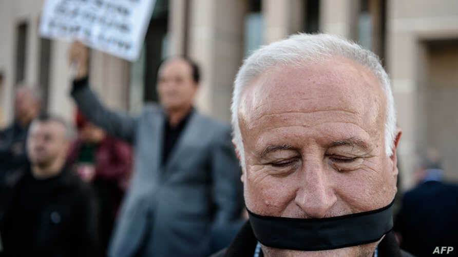 A demonstrator with his mouth covered, stands outside the Istanbul courthouse, where Turkish opposition Cumhuriyet daily's editor-in-chief Can Dundar and Ankara bureau chief Erdem Gul attend their trial, April 1, 2016.