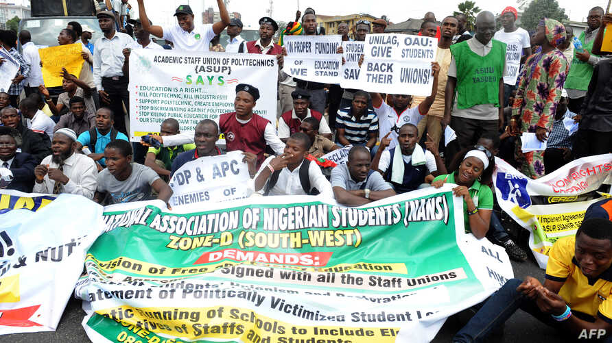 Students and workers carry placards as they sit on the Lagos-Ikorodu highway to protest against the suspension of academic activities following a nationwide strike by lecturers in state-owned universities, Aug. 13, 2013 in Lagos.