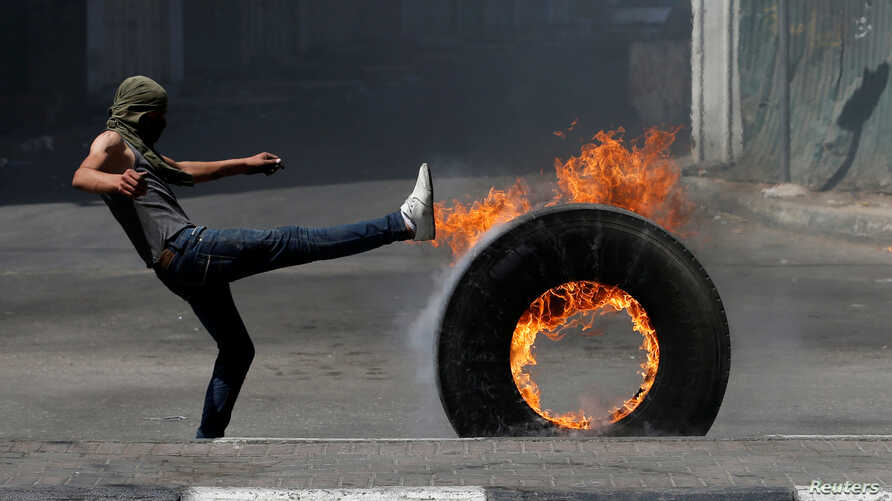 A Palestinian protester rolls a burning tire during clashes with Israeli troops in Hebron in the occupied West Bank, July 27, 2018.