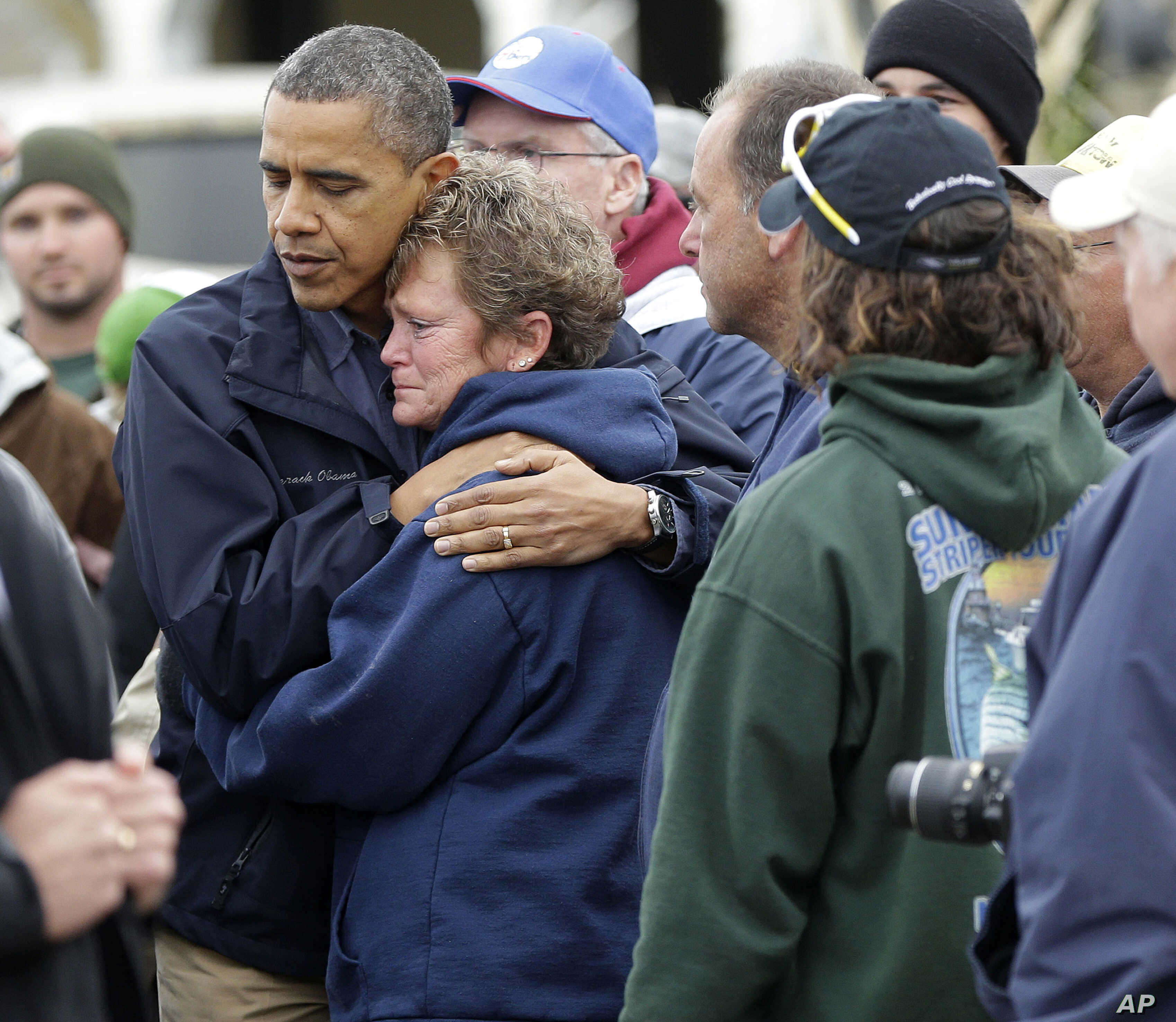 President Barack Obama, left, embraces Donna Vanzant, right, during a tour of a neighborhood effected by superstorm Sandy, Oct. 31, 2012 in Brigantine, N.J.