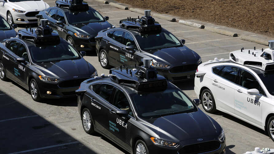 A group of self-driving Uber vehicles position themselves to take journalists on rides during a media preview at Uber's Advanced Technologies Center in Pittsburgh, Pennsylvania, Sept. 12, 2016.