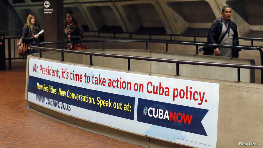Commuters walks past a poster urging U.S. President Barack Obama to change U.S. policy towards Cuba at the McPherson Square Metro stop in Washington, D.C., April 28, 2014.
