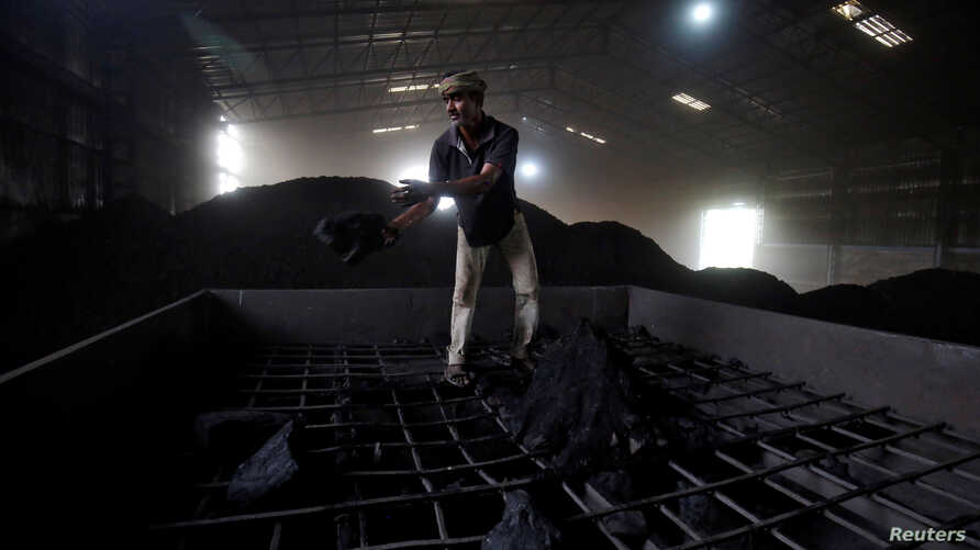 A laborer works inside a coal yard on the outskirts of Ahmedabad, India, April 6, 2017.