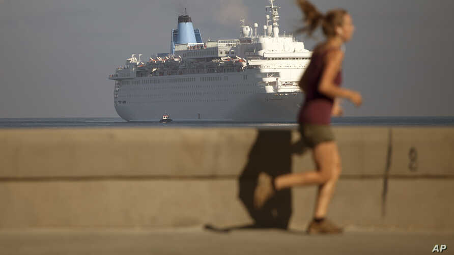 A woman jogs on the Malecon as the Thomson Dream cruise ship arrives in Havana bay, Cuba, March 19, 2015.