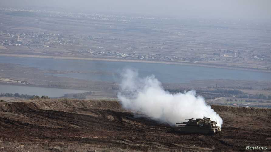 An Israeli tank maneuvers close to the ceasefire line between Israel and Syria on the Israeli-occupied Golan Heights, November 13, 2012.