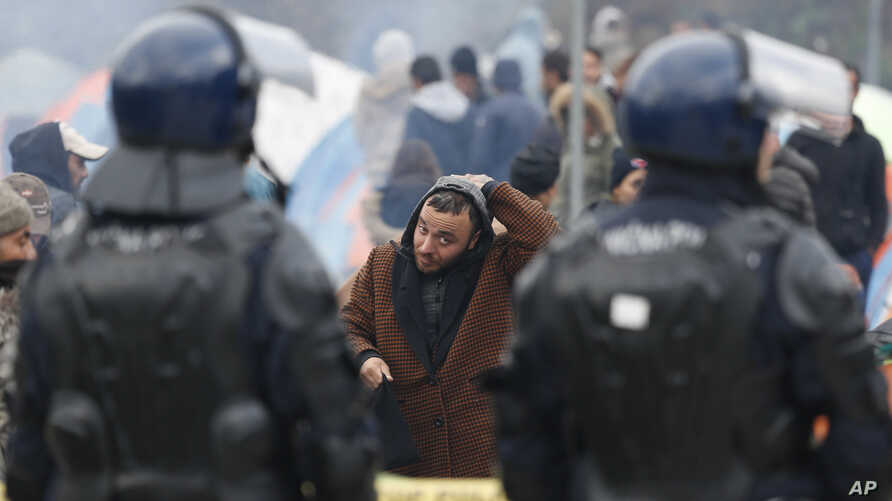 FILE - A migrants adjust his his headcover as he walks in front of a Bosnian police cordon at the border crossing in Maljevac, Bosnia, Oct. 26, 2018.