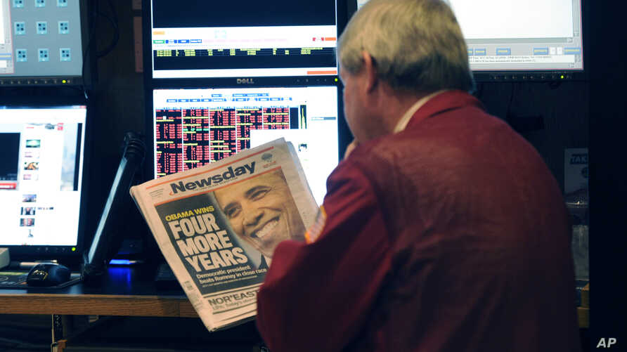 A trader on the floor of the New York Stock Exchange looks at the front page of a newspaper the day after Presiden Obama was re-elected, New York, November 7, 2012.