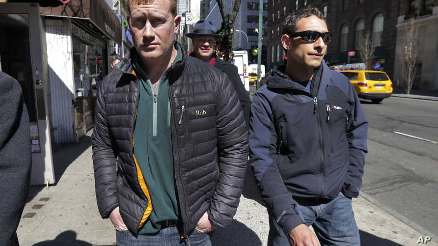 James Brady, left, and Andrew Rossig, right, two parachutists who jumped from One World Trader Center in September 2013, are accompanied by attorney Timothy Parlatore to surrender to police, in New York,  March 24, 2014.