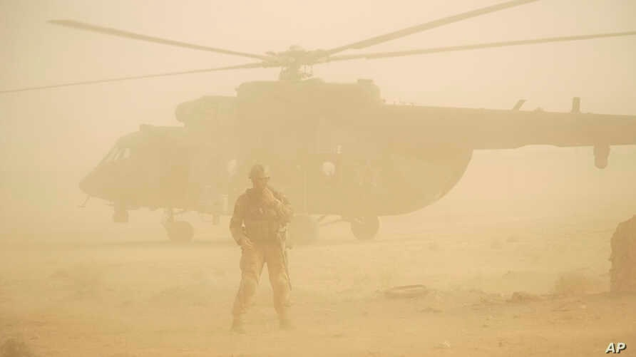 FILE -  Russian soldier stands guards as military helicopter takes off at an airport in Deir el-Zour, Syria, Sept. 15, 2017.