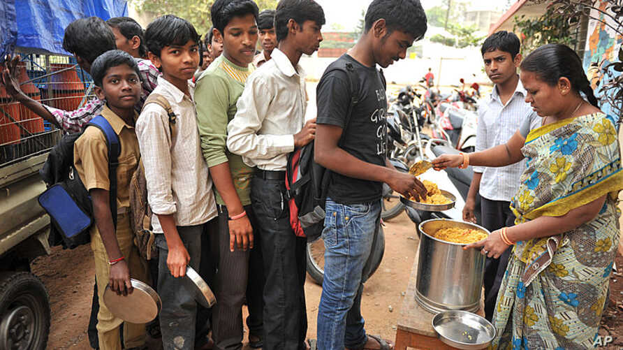 An Indian teacher serves the mid-day meal to children at a Government High School in Hyderabad, on January 10, 2012. (AFP)