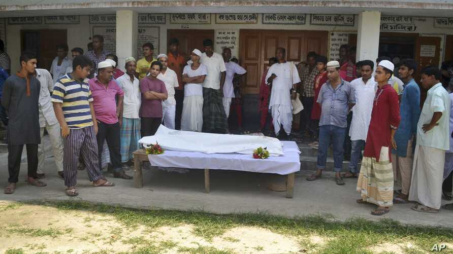 Locals surround the body of a Hindu holy man after assailants hacked him to death in Pabna, 275 kilometres (170 miles) from Dhaka, June 10, 2016.