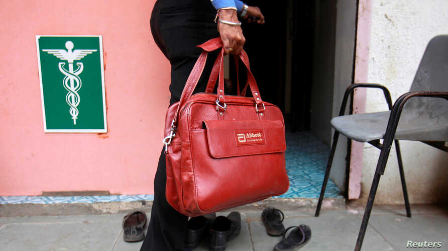 FILE - A representative for drugmaker Abbott enters a doctor's clinic in Pune, Aug. 27, 2012.