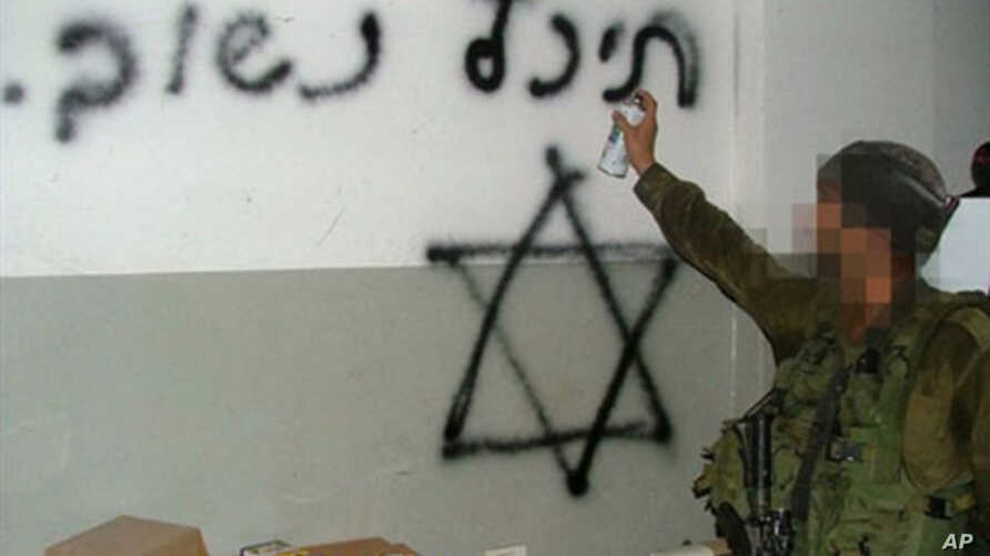 """A handout picture obtained by AFP from the Israeli human rights organization Breaking the Silence on 25 October 2010 allegedly shows an Israeli soldier spray-painting a Star of David and the Hebrew writing """"Back soon"""" on what appears to be the wall o"""