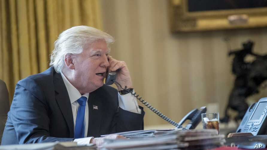 President Donald Trump speaks on the phone with Russian President Vladimir Putin, Jan. 28, 2017, in the Oval Office at the White House in Washington.