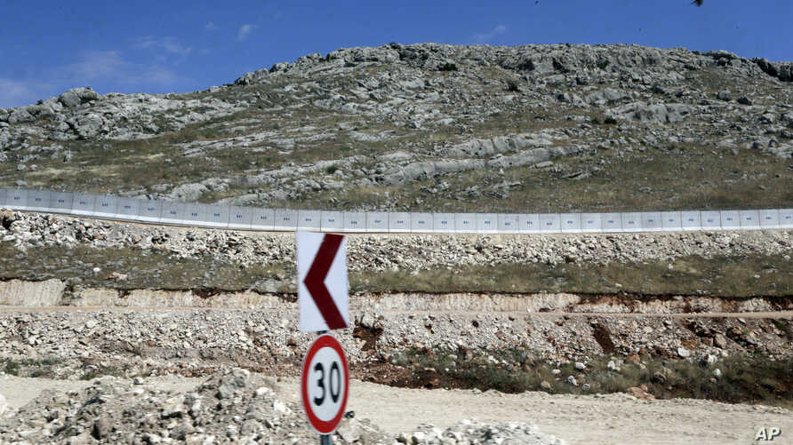 FILE - A newly built wall near Cilvegozu border gate in Reyhanli, at the Turkey-Syria border, May 24, 2017. Turkish President Recep Tayyip Erdogan says his country plans to build walls along its borders with Iraq and Iran, similar to the one currentl