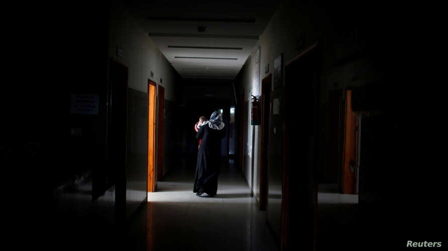 A Palestinian woman carries her sick child as she walks through the corridor at Durra hospital in Gaza City, Feb. 6, 2018.