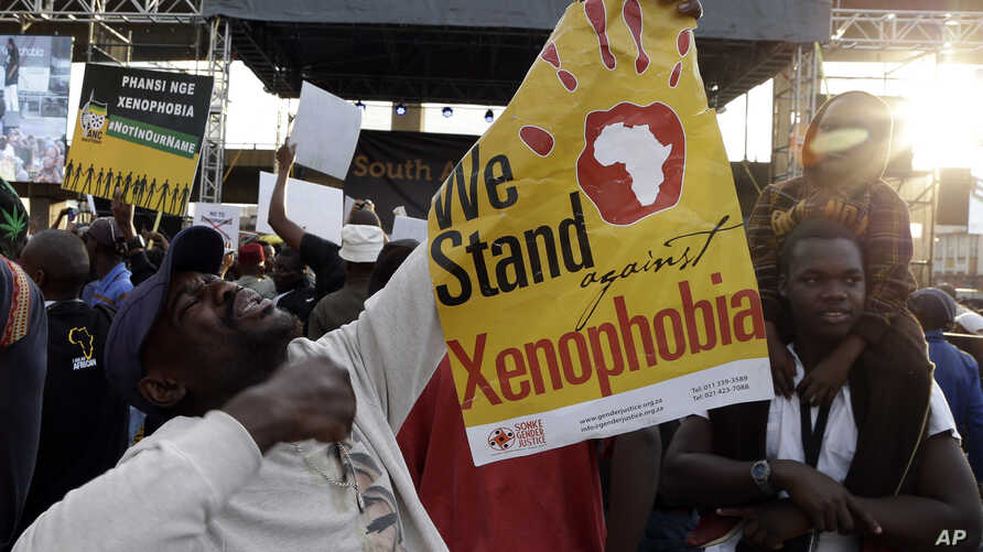 """FILE - A man holds a poster reading """"we stand against xenophobia""""  during a march in Johannesburg, South Africa, protesting against recent attacks on immigrants that killed seven people, April 23, 2015."""