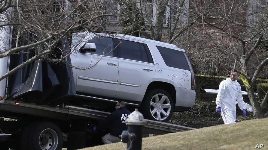 """FILE - Investigators load a car that appears to have been checked for fingerprints onto a flatbed truck in the Staten Island borough of New York, March 14, 2019.  Francesco """"Franky Boy"""" Cali was found with multiple gunshot wounds at his red-brick col"""