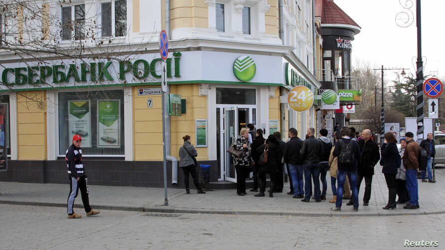 People stand in a line as they wait to enter a branch of Sberbank of Russia bank in the Crimean city of Simferopol April 4, 2014. REUTERS/Stringer (UKRAINE - Tags: BUSINESS) - RTR3JYJ0