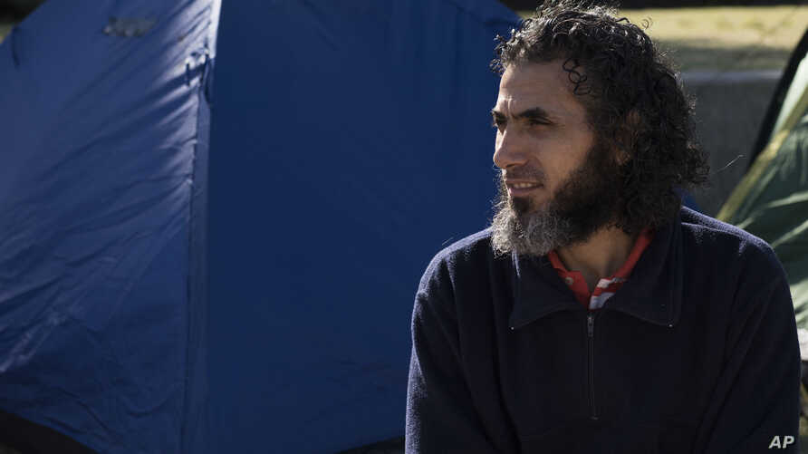 FILE - Abu Wa'el Dhiab, from Syria, sits in front of the U.S. embassy while visiting former fellow detainees demanding financial assistance from the U.S., in Montevideo, Uruguay, May 5, 2015.