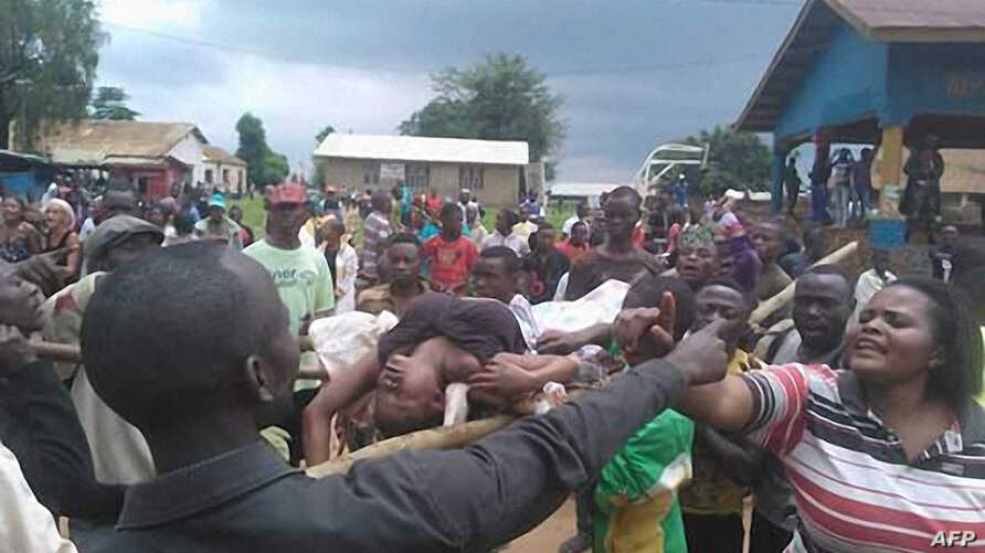People argue as a woman is transported to the hospital in Beni on Aug. 15, 2016 following a wave of unrest and violence in the region.