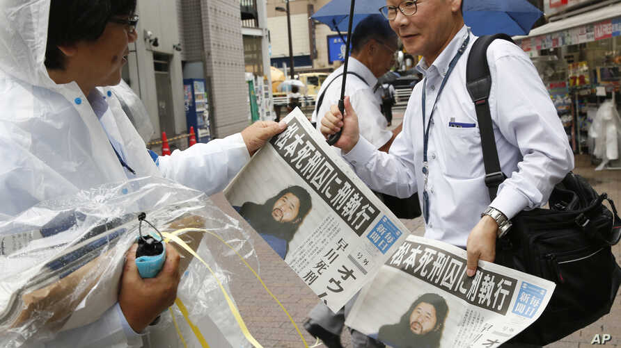 A staff member of the Japanese newspaper Mainichi Shimbun distributes their extra edition reporting that doomsday cult leader Shoko Asahara was executed, in Tokyo, July 6, 2018. Japan executed the last six members of the cult Thursday.