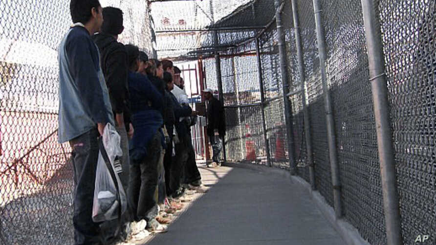Illegal immigrants from Mexico wait in a holding area in El Paso, Texas, May 1, 2008.