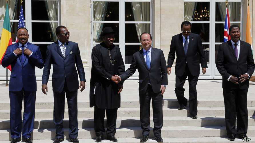 French President Francois Hollande, third right, shakes hands with Nigeria President Goodluck Jonathan, third left, as other leaders look on for family photo in Paris, May 17, 2014.