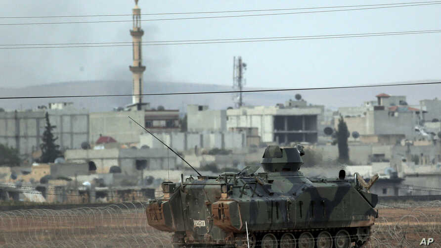 Backdropped by Kobani, in Syria, a Turkish forces armoured vehicle patrols the border road in Mursitpinar, on the outskirts of Suruc, on the Turkey-Syria border, Oct. 14, 2014.