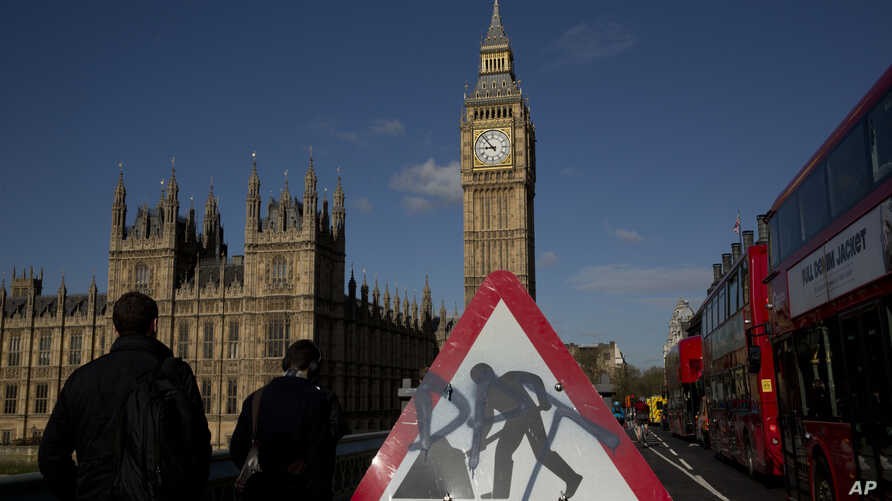 A road work sign stands on Westminster Bridge, near the Houses of Parliament and Elizabeth Tower, which houses the Big Ben bell in London, April 26, 2016. Officials say the chimes of Britain's Big Ben bell will fall silent for several months during a