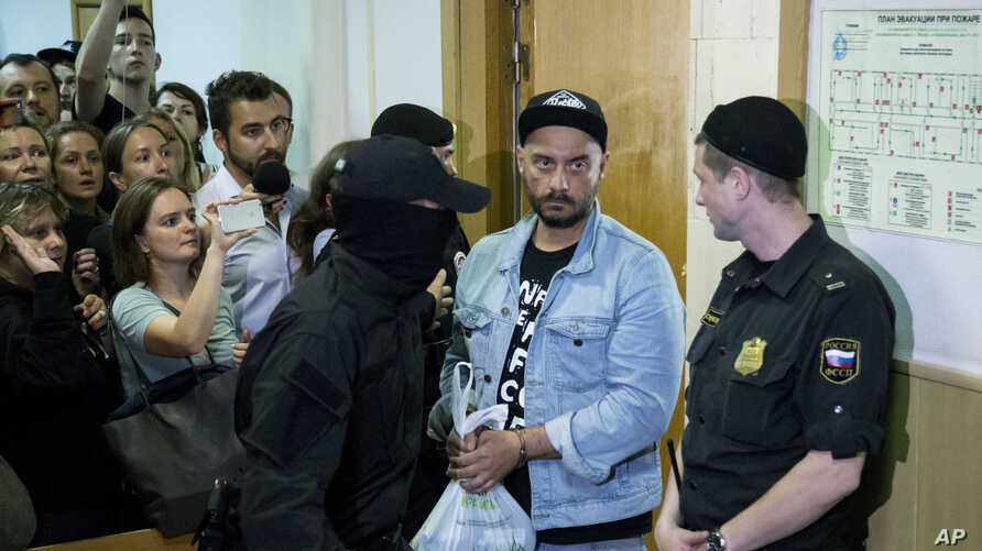 Russia's theater and film director Kirill Serebrennikov, second from right, is escorted in  for hearings in a court in Moscow, Russia, Wednesday, Aug. 23, 2017.