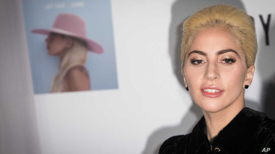 Singer Lady Gaga poses for photographers during a photo call before her surprise acoustic performance in London, Dec. 1, 2016.
