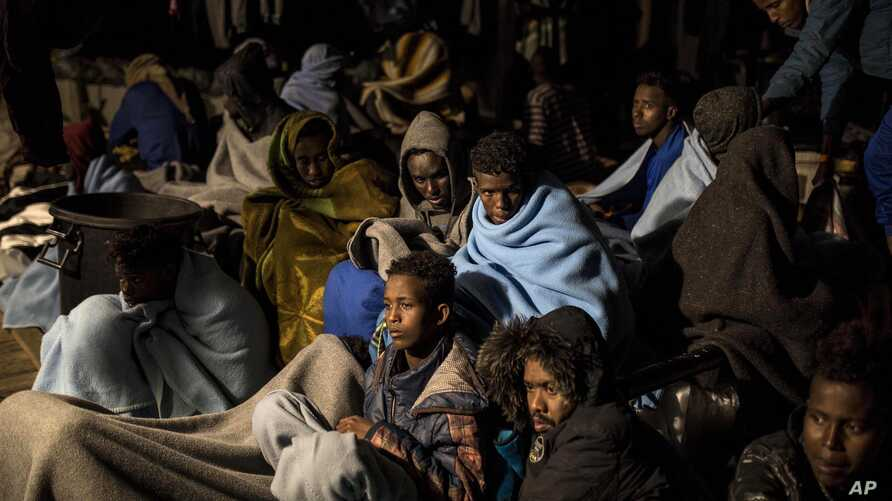 FILE - In this photo taken on Sunday Feb. 18, 2018 photo, refugees and migrants sit on the deck of a rescue ship after being rescued by aid workers of the Spanish NGO Proactiva Open Arms.