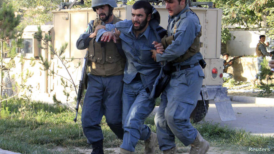 Afghan policemen help an injured comrade at the site of a suicide bomb attack in Ghazni Province, September 4, 2014.