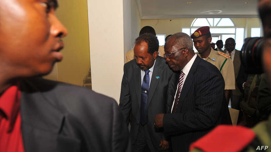 Somalia's newly elected President Hassan Sheikh Mohamud (C) and Kenya's Foreign Affairs Minister Sam Ongeri (2nd R) leave the Jazeera hotel after a bomb blast outside the venue in Mogadishu, September 12, 2012.