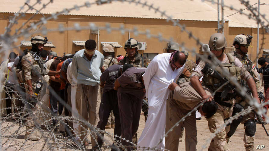 FILE - Blindfolded and handcuffed suspected al-Qaida members are led away to detention centers in an Iraqi army base in Hillah, Iraq, July 20, 2012.