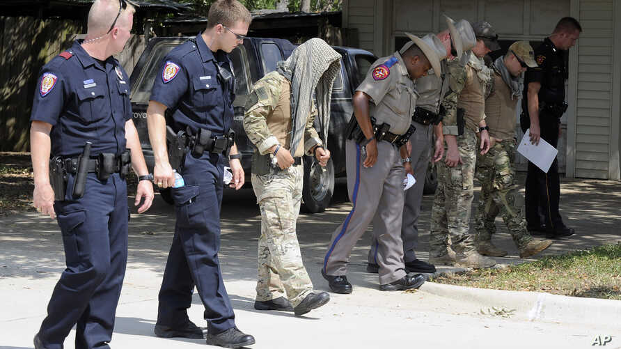 Law enforcement officials conduct a grid search of an area where police say a gunman was being served an eviction notice when he opened fire from inside a home near Texas A&M and killed a law enforcement officer  Monday, Aug. 13, 2012, in College Sta