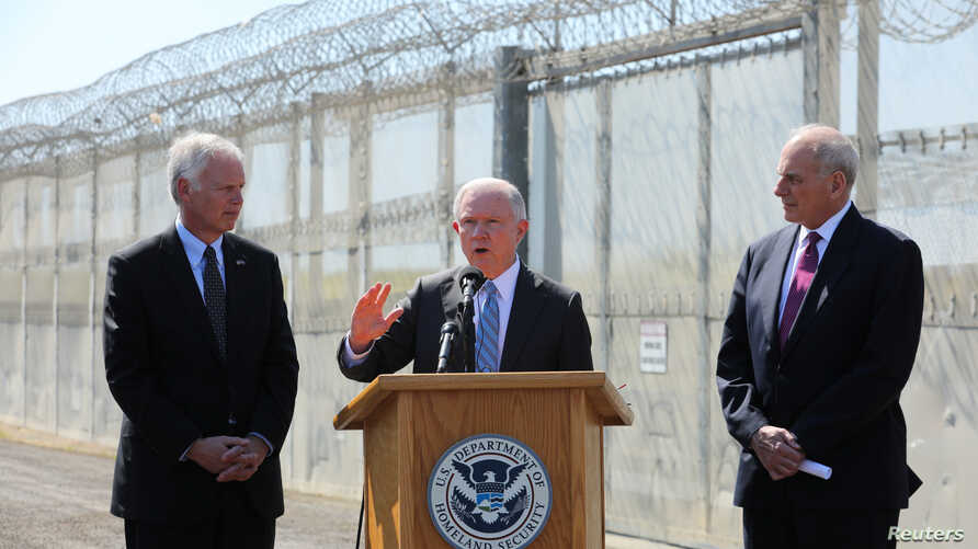 U.S. Attorney General Jeff Sessions speaks as Secretary of Homeland Security John Kelly, right, and U.S. Senator Ron Johnson look on while visiting the U.S.-Mexico border area in San Diego, California, April 21, 2017.