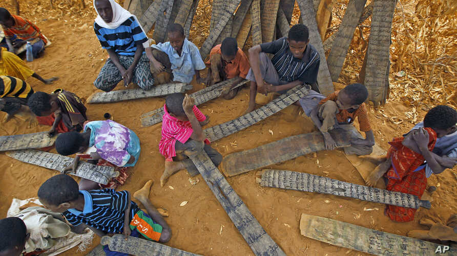 Young Somali refugees read verses of the Koran from their prayer tablets at an outdoor madrasa at the Ifo camp outside Dadaab, Eastern Kenya, 100 kms (60 miles) from the Somali border, Aug. 9, 2011.