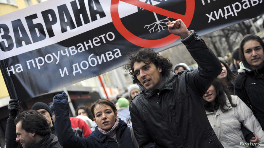 """FILE - People shout slogans and carry a banner that reads """"Ban the shale gas tests through hydraulic fracturing"""" during a rally in central Sofia January 14, 2012."""