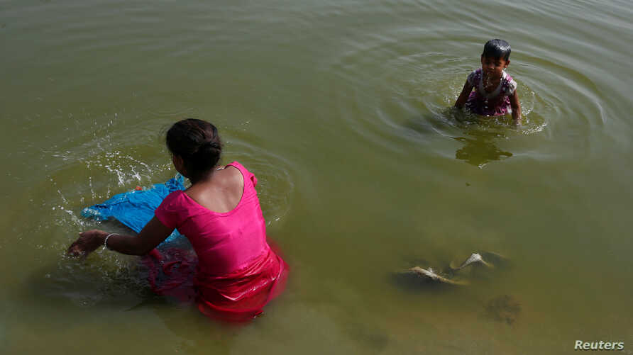 FILE - A woman washes clothes as her daughter bathes in the Yamuna River on a hot day in New Delhi, India, April 24, 2017.